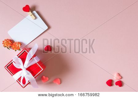 Valentine day composition: red gift box with bow credit / visiting card template with clamp spring flowers and small hearts on light pink background. Top view.