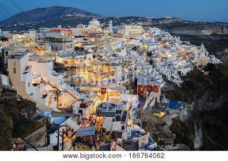 Fira, Santorini island, Greece - April 2016: Illuminated Luxury balcony decks and patios with restaurants of Fira town at Santorini island, just after sunset. Santorini is one of most famous greek