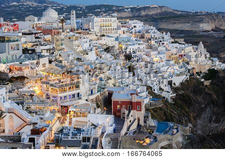 Fira, Santorini island, Greece - April 2016: Illuminated Luxury balcony decks and patios with restaurants of Fira town at Santorini island, after sunset. Santorini is one of most famous greek resorts