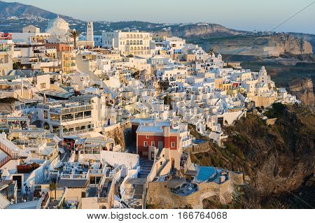 Fira, Santorini island, Greece - April 2016: Illuminated Luxury balcony decks and patios with restaurants of Fira town at Santorini island, in warm rays of sunset. Santorini is one of most famous