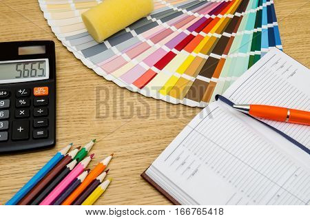 color swatches pencil pen notebook calculator on wooden table