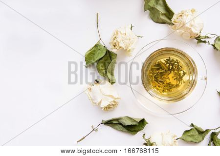 Cup of green tea with dry white roses around. Square. Isolated. Toned.