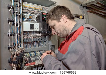 St. Petersburg Russia - March 5 2013: Engineer electrician fixes problems in the electrical switchboard.