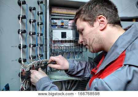 St. Petersburg Russia - March 5 2013: Mechanical Engineer doing upgrade equipment electrical switchboard.