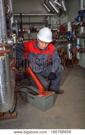 St. Petersburg Russia - March 5 2013: Mechanical engineer makes hydraulic tests of heating system using the Ridgid electric test pump.