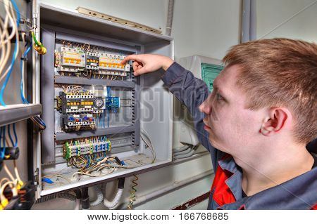 St. Petersburg Russia - March 5 2013: Engineer electrician carries out repair a circuit breaker in industrial switchboard.