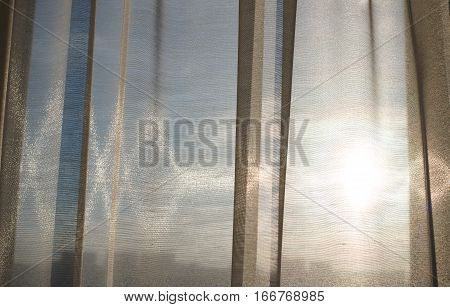 Morning sun shines through the curtains. Folds curtains. Fabric waves.