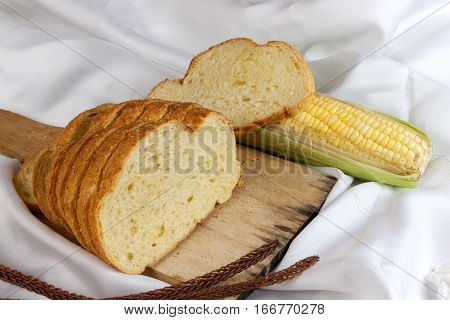 bread made from corn on the white fabric. Slices of corn bread laying on a chopping Board and Sweet corn cobs