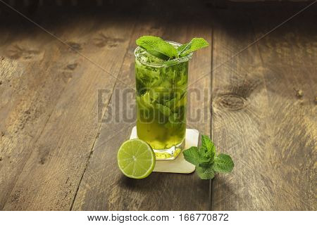 A photo of a mojito cocktail with mint leaves and a wedge of lime on a dark wooden background with copyspace