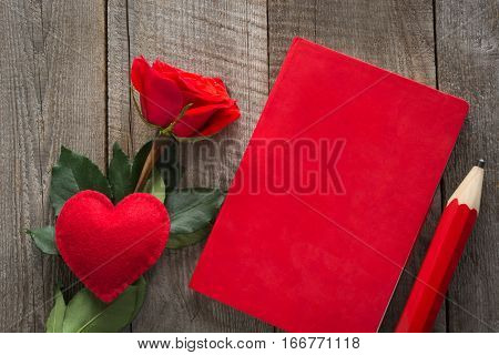 Valentine's card. Red rose heart and red notebook on wooden board. Top view.