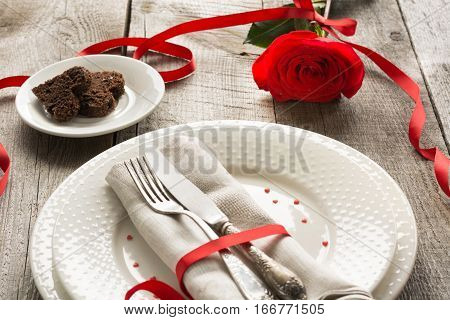 Romantic dinner concept. Festive table setting for Valentines Day on wooden background. Red rose with ribbon on table.