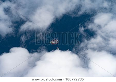 Top view of oil and gas drilling rig while drilling operation at oil and gas wellhead remote platform looking through cloud.