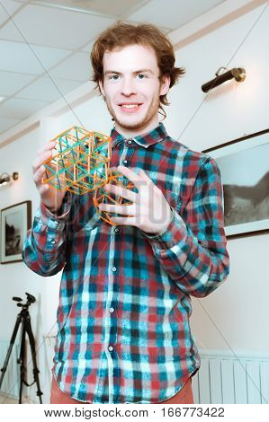 Young smiling man in a plaid shirt looking at the camera and holding coloured three-dimensional models of geometric solids.