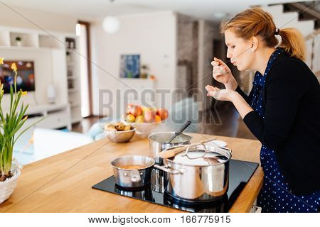 Housewife Tasting Food Being Made In Kitchen