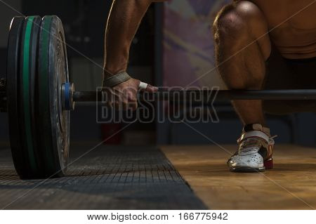 Young Muscular Man Lifting Barbell In Gym, Closeup
