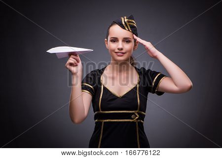 Young flight attendant on gray background