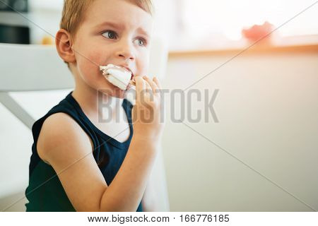 Beautiful child earing icecream in living room