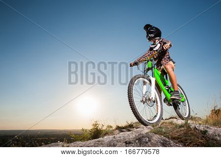 Cyclist With Mountain Bike On The Hill Under Blue Sky