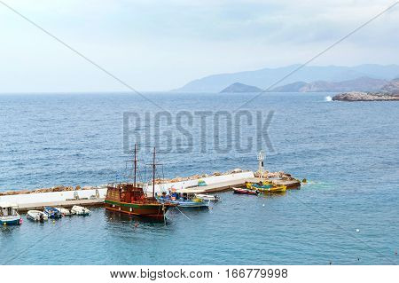 Harbour with marine vessels boats and lighthouse. View from cliff on Bay with marine braid. Bali - vacation destination resort with secluded beaches and clear ocean waters. Rethymno Crete Greece