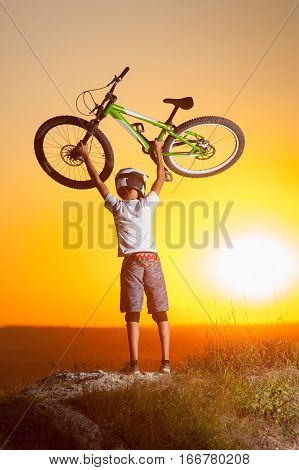 Cyclist With Mountain Bike On The Hill In The Evening