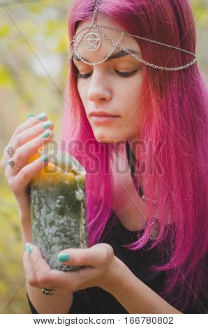 Young witch with pink hair performing a magical ritual with a large green candle faded colors selected focus