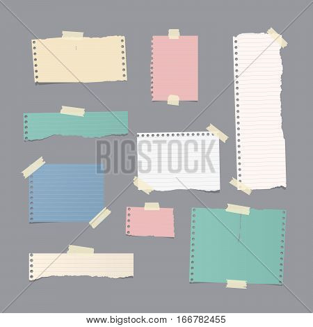 Pieces of different size ruled and blank colorful note, notebook, copybook paper sheets, strips stuck with sticky tape on gray background.