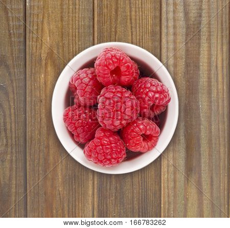 Raspberries in a white ceramic bowl. Top view. Ripe and tasty raspberries on a wooden background.