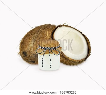 Jar of coconut oil and fresh coconuts isolated on white background. Coconut nuts with leaves.