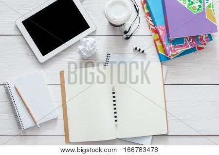 Student table background. Modern white office desk with tablet, books and other supplies with coffee take away cup. Blank open diary with copy space for text. Top view, flat lay.