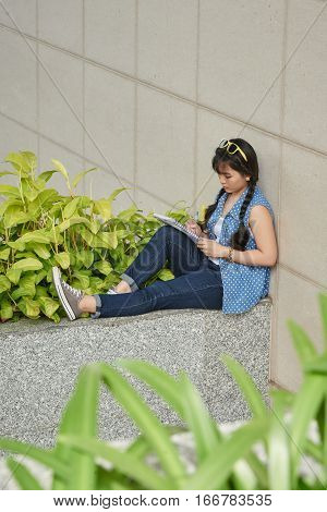 Vietnamese college girl sitting outdoors and taking notes in textbook