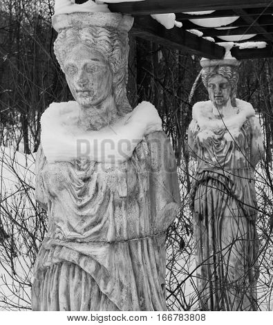 Sculpture Of A Caryatids In Winter Park Covered With Snow.