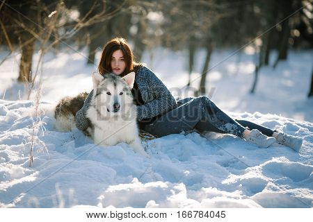 Girl with dog malamute lies on snow in winter forest. She hugged dog.