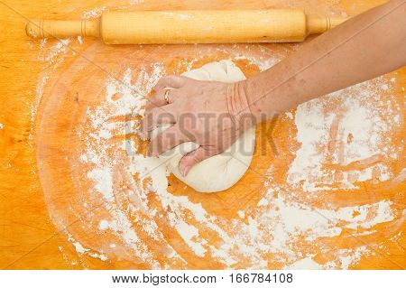 Man unrolls dough on board with rolling pin and flour
