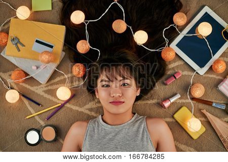 Pretty teenage girl lying on the floor, her belongings and string of bulbs around