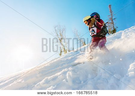 Freerider Girl Snowboarder Slides From The Mountain In The Light Of The Sun