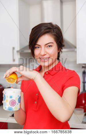Girl prepares tea with lemon in kitchen