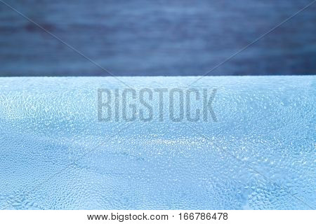 Close up drops of ice cold bottle of water on wood background