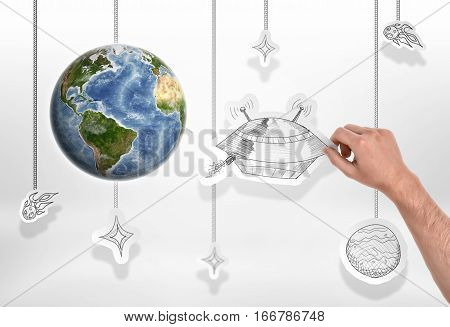 Earth with man's hand holding a picture of big UFO on the white background. Creativity and art. Fantasy and science fiction. Intruder alert. Elements of this image are furnished by NASA.