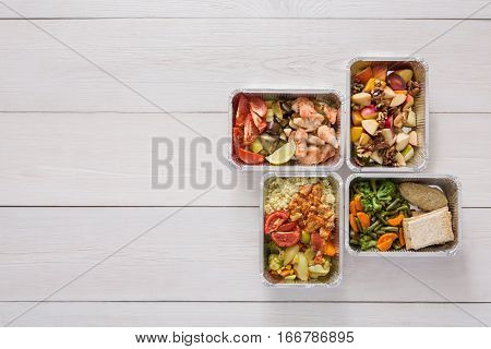 Healthy food delivery. Take away of natural fitness dishes for diet. Daily meals in foil boxes. Vegetables, salmon, meat and salads. Top view, flat lay, copy space on white wood