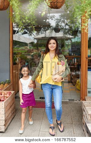 Smiling Indian mother and daughter leaving grocery store