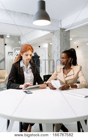Two attractive businesswomen using technology while sitting in immaculate office