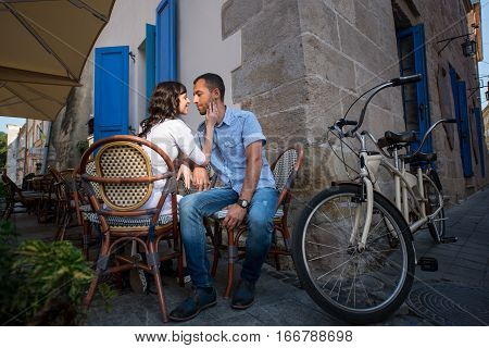 Lovely Couple Sitting In Sidewalk Cafe Near Their Tandem Bicycle