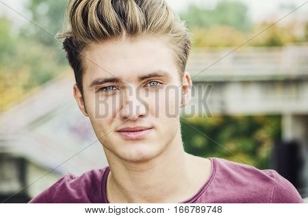 Handsome blond young man head-shot outdoors, looking at camera