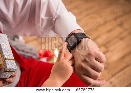 Cropped image of hand with smartwatch and child finger pointing on it