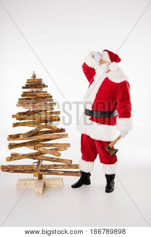 Tired Santa Claus making Christmas tree from firewood on white