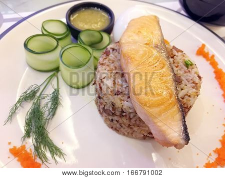 Fried salmon on the rice served with preserved cucumber and sour sauce - thai fusion food
