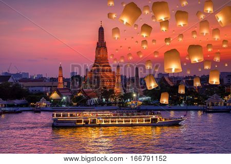Wat arun and cruise ship in night time and floating lamp in yee peng festival under loy krathong day Bangkok city Thailand