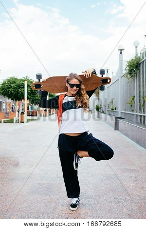 Longboard girl on the street. smiling young woman with a longboard and sunglasses standing on the street.