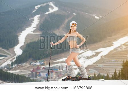 Smiling Naked Sexy Woman Is Standing On The Top Of The Slope With Skis. Wearing Boots, Helmet And Su