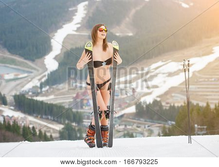 Smiling Naked Sexy Woman Is Standing On The Top Of The Slope With Skis